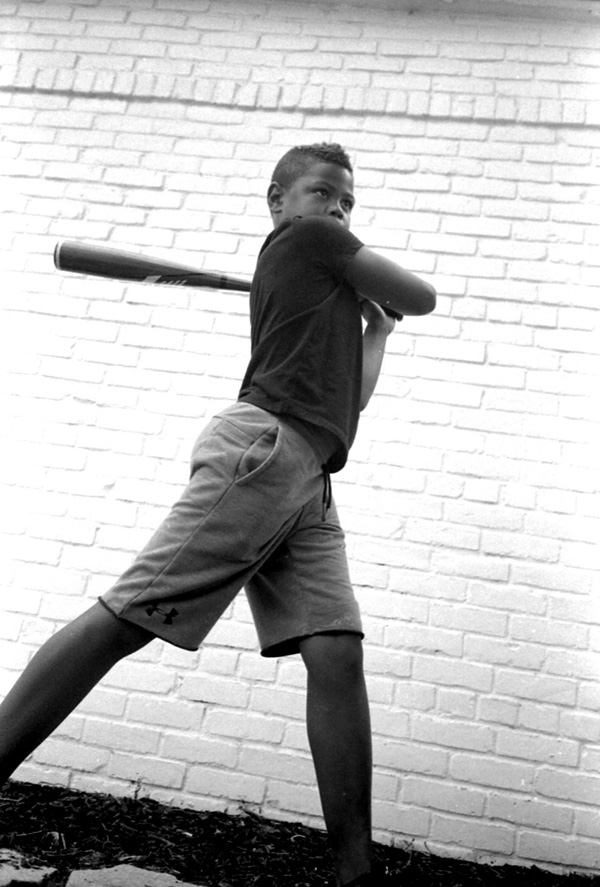 Young Boy with a black t-shirt holding a baseball bat and resting